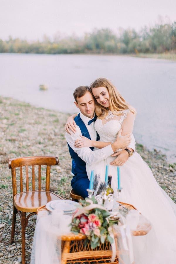Retrato al aire libre sensible de la novia que se sienta en el novio en la costa fotos de archivo