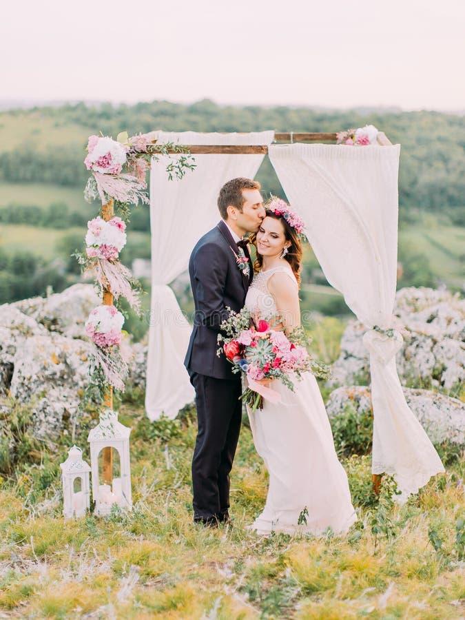 Retrato al aire libre sensible del novio que besa a la novia en la frente cerca del arco de la boda en las montañas foto de archivo libre de regalías