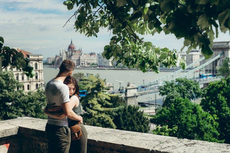Retrato al aire libre sensual de los pares cariñosos encantadores que abrazan suavemente en el balcón en el backgroud de la Budap imagen de archivo libre de regalías