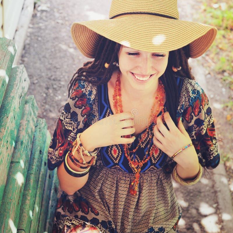 Retrato alegre da jovem mulher com os dreadlocks vestidos no vestido do estilo do boho e na colar, exterior ensolarado fotografia de stock royalty free