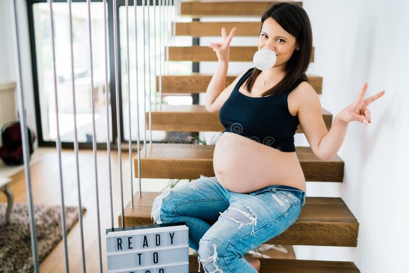 Retrato alegre de la mujer embarazada joven que se sienta en las escaleras que disfrutan de vida detalles modernos de la forma de imagenes de archivo