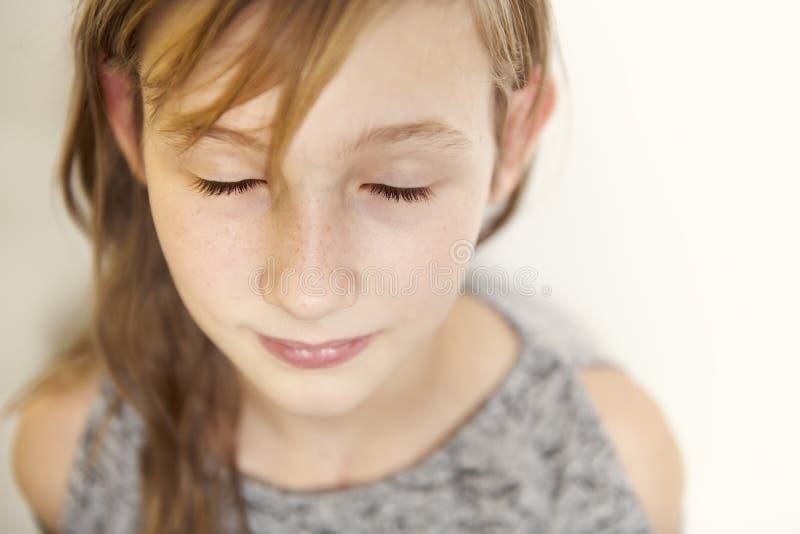 Retrato alegre lindo de la niña, aislado en la cabeza roja del fondo gris fotos de archivo