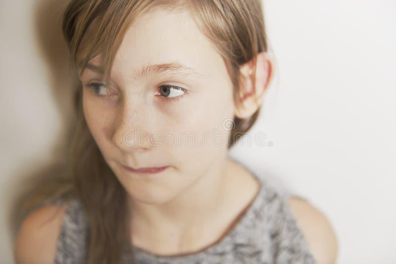 Retrato alegre lindo de la niña, aislado en la cabeza roja del fondo gris imagen de archivo libre de regalías