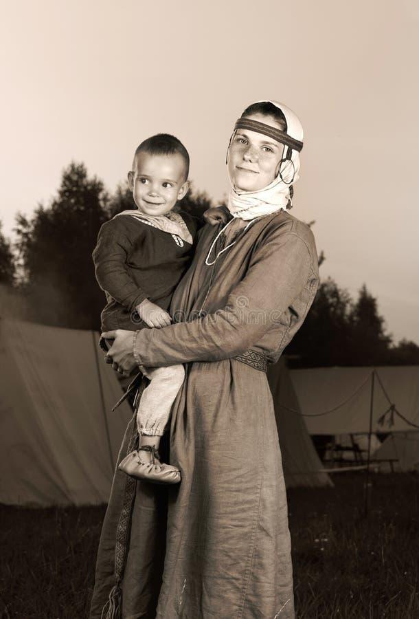 Retrato antiguo teñido de una mujer eslava con un niño en historia del costumu fotos de archivo libres de regalías