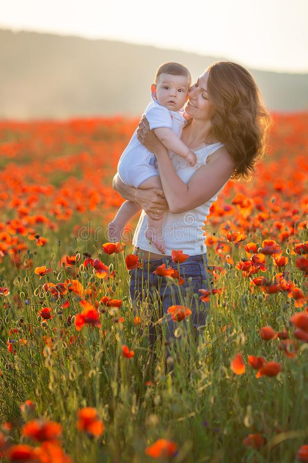 Retrato ao ar livre A mãe nova e sua filha apreciam o tempo da vida junto em um campo da papoila Conceito do amor e da família fe imagem de stock