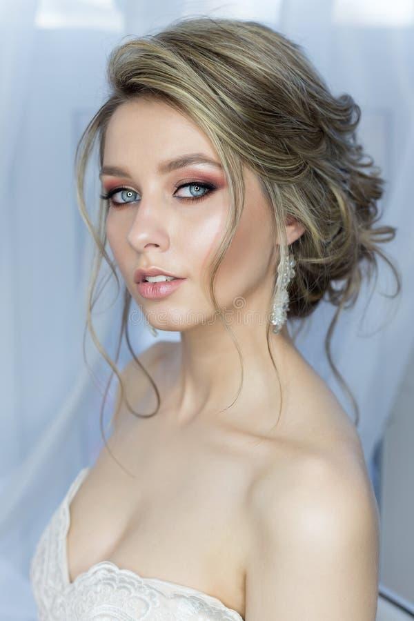 Retrato apacible de una novia feliz linda hermosa con un maquillaje brillante festivo del peinado hermoso en un vestido de boda c fotografía de archivo