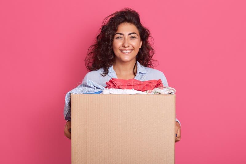 Retrato aproximado de feliz morena caucasiana segurando caixa de cartão com doação, adorável mulher posando isolada sobre rosa imagem de stock royalty free