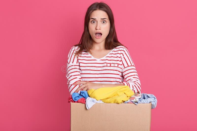 Retrato aproximado de surpreendente mulher com boca aberta, senhora com expressão facial surpreendida segurando caixa com roupas, fotografia de stock royalty free