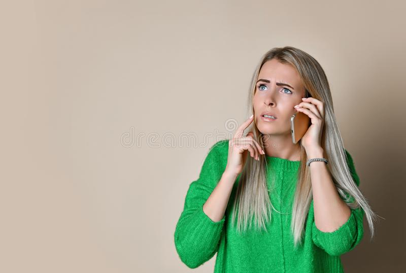 Retrato ascendente cercano de la chica joven en mirada verde del suéter a un lado y hablar en el teléfono digital moderno del art imagenes de archivo