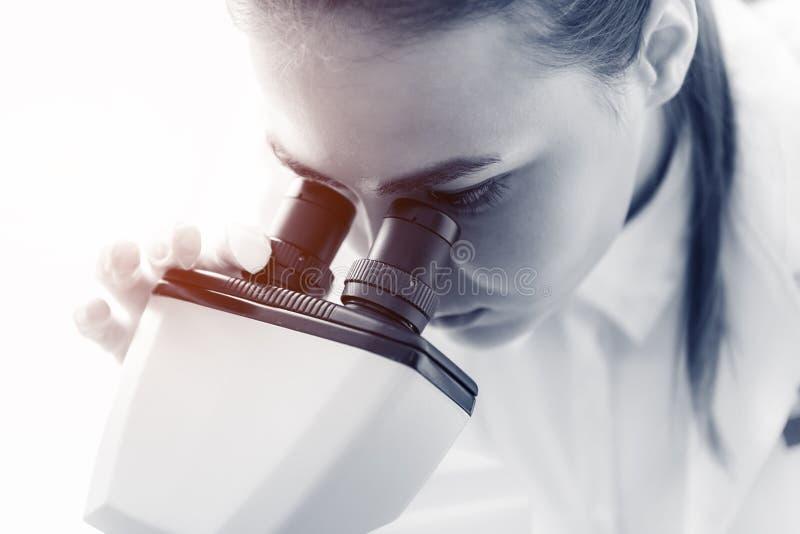 Retrato ascendente cercano de la investigación joven del científico usando el microscopio i imagenes de archivo