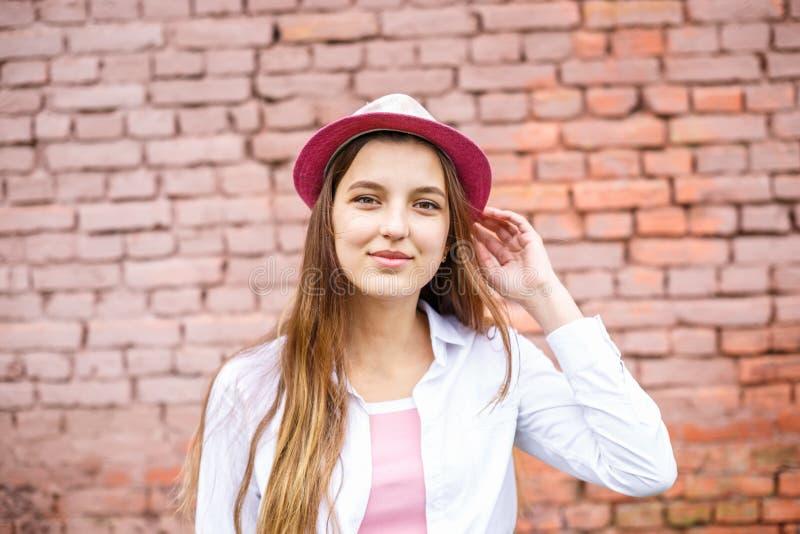 Retrato ascendente cercano de la muchacha elegante hermosa del ni?o en sombrero cerca de la pared de ladrillo rosada como fondo imagen de archivo libre de regalías