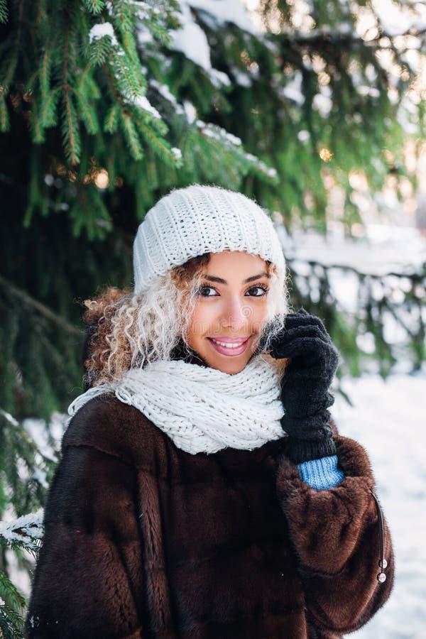 Retrato ascendente cercano de la muchacha hermosa joven con el pelo afro en bosque del invierno La Navidad, concepto de las vacac foto de archivo libre de regalías