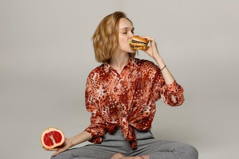 Retrato ascendente cercano de la muchacha rubia bonita que come la hamburguesa imagenes de archivo