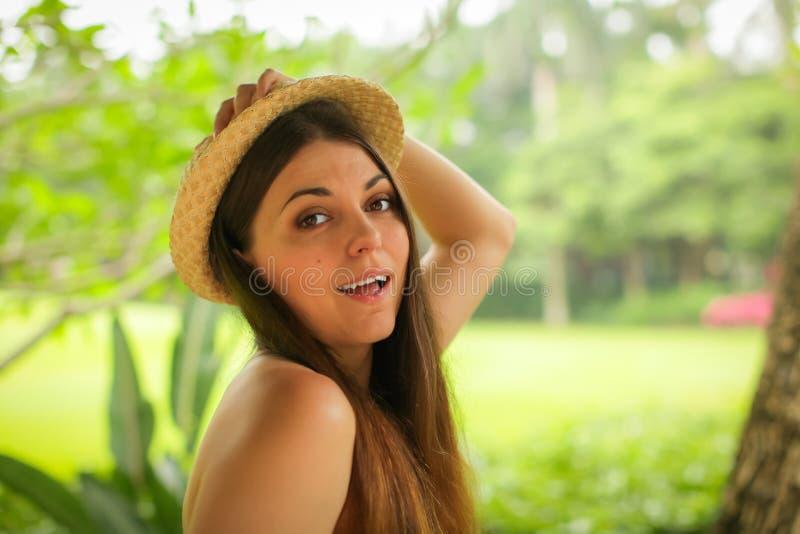 Retrato ascendente cercano de la mujer joven caucásica despreocupada con el sombrero de paja que presenta con diversas emociones  imagenes de archivo