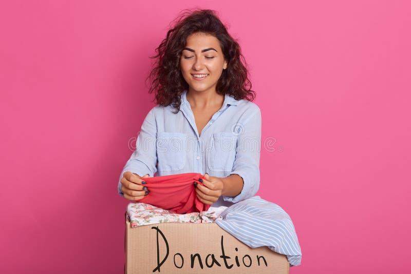 Retrato ascendente cercano de la mujer joven con el pelo ondulado oscuro, presentando cerca de la caja de la donación de la ropa, foto de archivo libre de regalías