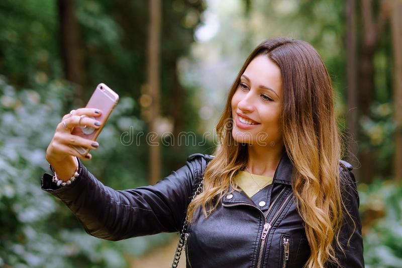 Retrato ascendente cercano de la mujer joven feliz que sonríe y que toma el selfie imagenes de archivo