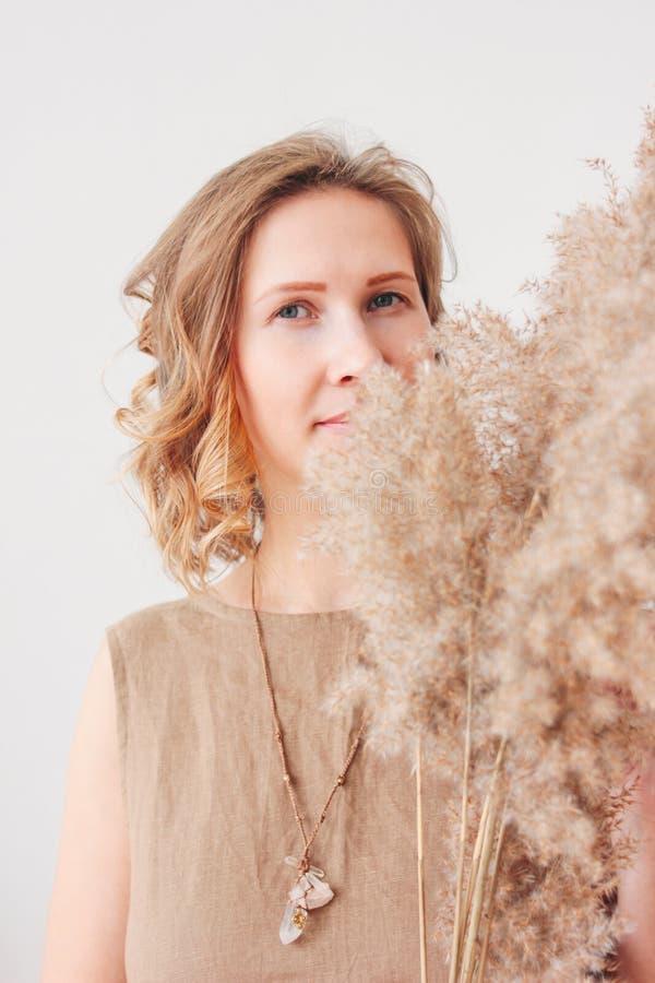 Retrato ascendente cercano de la mujer joven hermosa en el vestido de lino con las flores secadas, concepto natural de la belleza imagen de archivo libre de regalías