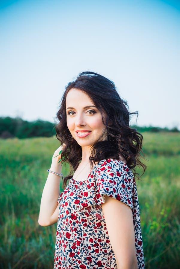 Retrato ascendente cercano de la mujer joven o de la muchacha cauc?sica en prado verde que disfruta de verano de la naturaleza Ca fotos de archivo