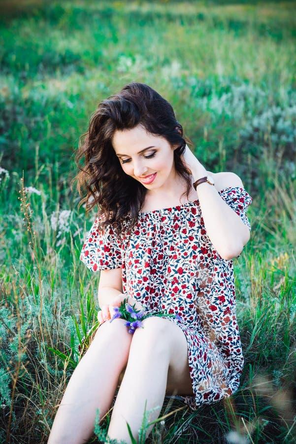 Retrato ascendente cercano de la mujer joven o de la muchacha romántica caucásica en prado muy verde que disfruta de verano de la foto de archivo libre de regalías