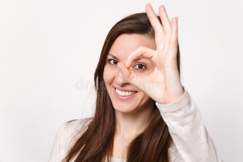 Retrato ascendente cercano de la mujer joven sonriente en la ropa ligera que mira gesto de la AUTORIZACIÓN de la demostración de  fotos de archivo