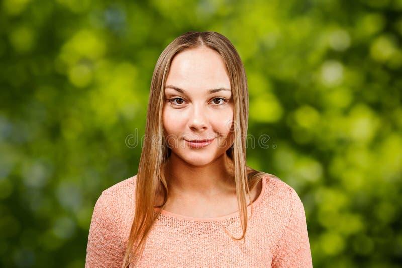 Retrato ascendente cercano de la mujer joven sonriente hermosa en una camisa beige, en fondo verde del bokeh imágenes de archivo libres de regalías