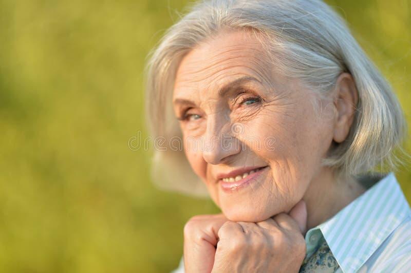 Retrato ascendente cercano de la mujer mayor hermosa feliz que presenta al aire libre foto de archivo