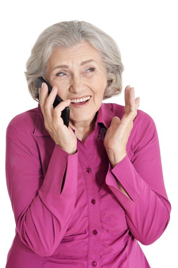 Retrato ascendente cercano de la mujer mayor hermosa que habla con smartphone en el fondo blanco imágenes de archivo libres de regalías