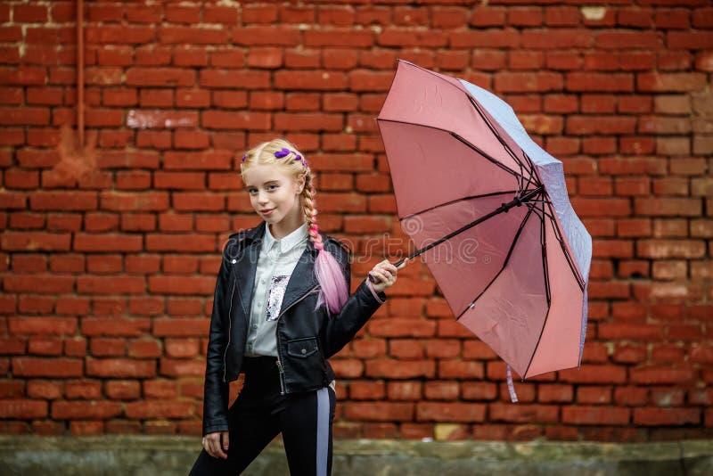 Retrato ascendente cercano de poca muchacha elegante hermosa del ni?o con un paraguas bajo la lluvia cerca de la pared de ladrill fotos de archivo