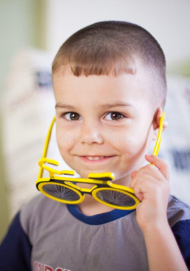 Retrato ascendente cercano de un pequeño muchacho sonriente en vidrios de un sol divertidos fotos de archivo