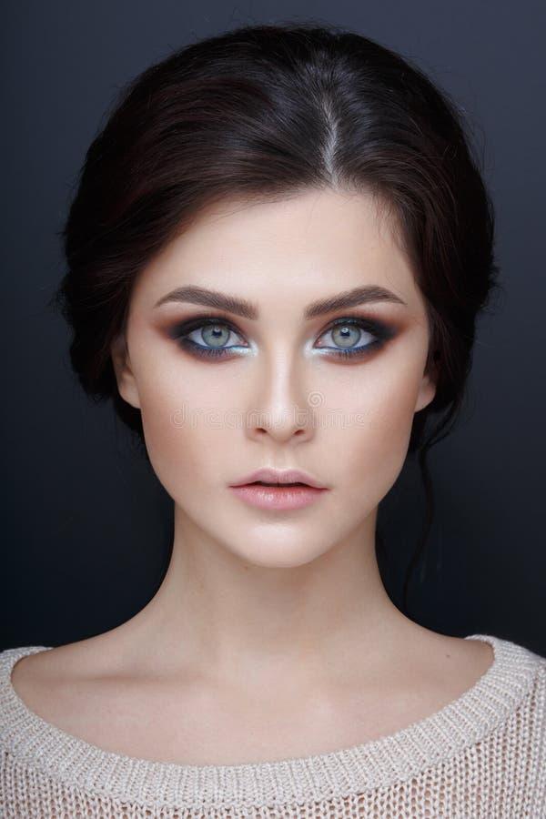 Retrato ascendente cercano de una muchacha beautyful con maquillaje perfecto Cara de una muchacha hermosa, en un fondo gris imágenes de archivo libres de regalías