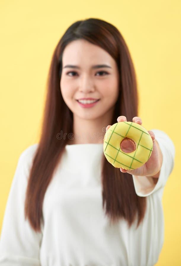 Retrato ascendente cercano de una muchacha linda que presenta con los anillos de espuma en fondo amarillo imagen de archivo