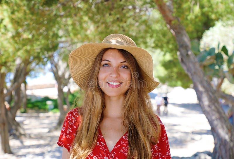 Retrato ascendente cercano de una muchacha sonriente hermosa con el pelo marrón que lleva un sombrero y que mira la cámara al air imágenes de archivo libres de regalías