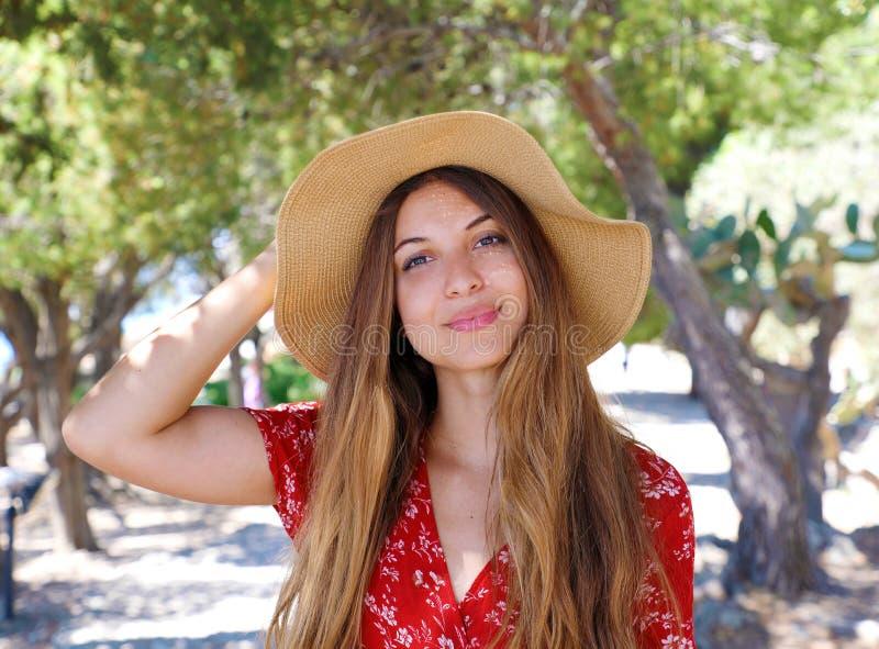 Retrato ascendente cercano de una muchacha sonriente hermosa con el pelo marrón que lleva un sombrero y que mira la cámara al air fotografía de archivo libre de regalías