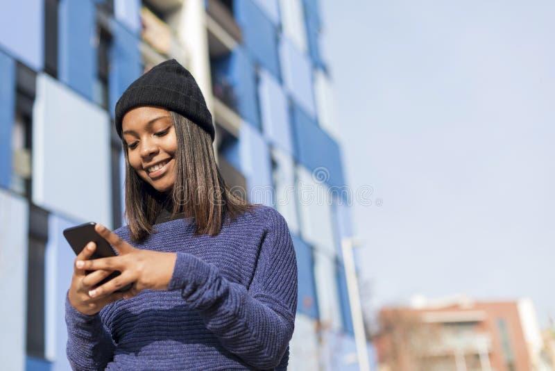 Retrato ascendente cercano de una mujer africana joven hermosa usando el teléfono móvil al aire libre en la ciudad foto de archivo libre de regalías