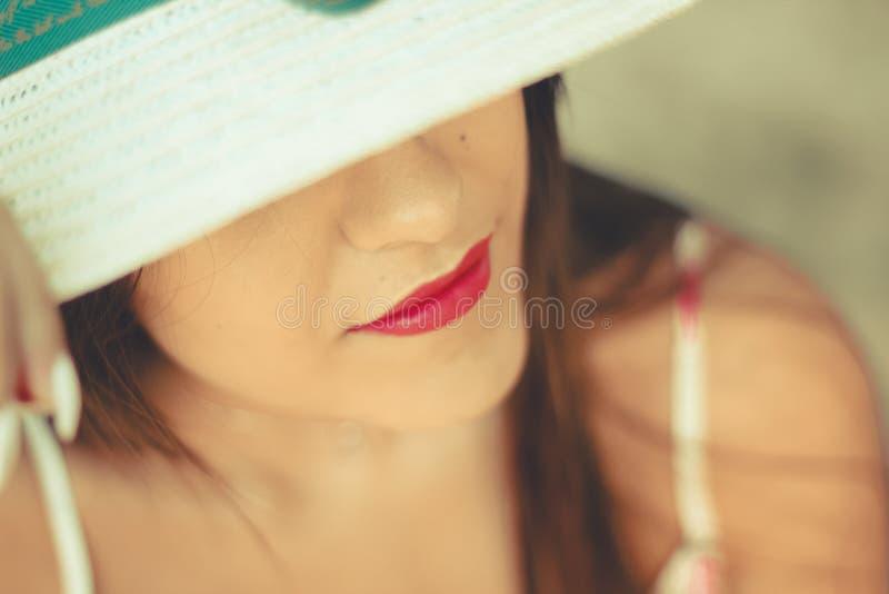 Retrato ascendente cercano de una mujer joven hermosa que lleva un sombrero blanco del sol fotografía de archivo libre de regalías