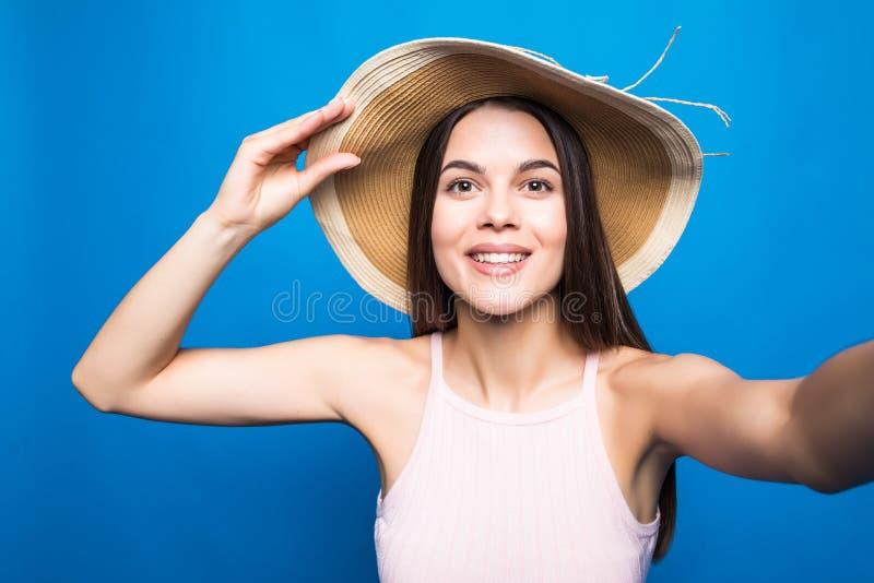 Retrato ascendente cercano de una mujer joven preciosa en el vestido del verano y el sombrero de paja que toman un selfie aislado fotografía de archivo