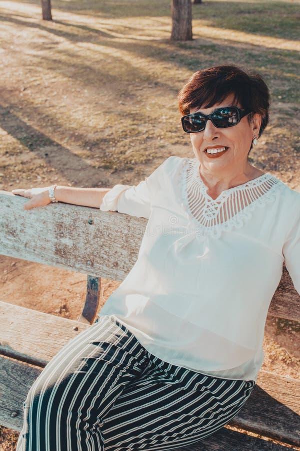Retrato ascendente cercano de una mujer mayor en el parque que se sienta en un banco en la puesta del sol foto de archivo