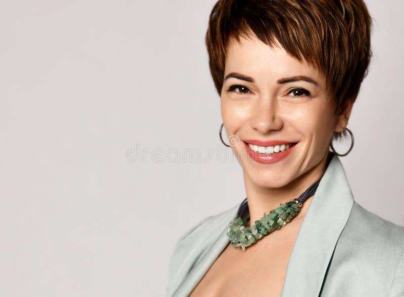 Retrato ascendente cercano de una mujer de negocios profesional del pelo corto que sonríe en gris fotos de archivo libres de regalías