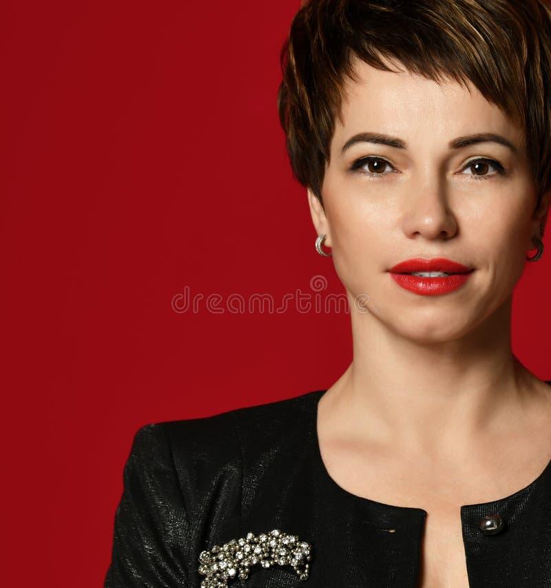 Retrato ascendente cercano de una mujer de negocios profesional del pelo corto que sonríe en rojo fotos de archivo