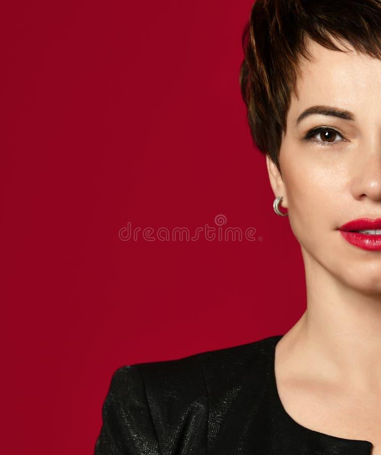 Retrato ascendente cercano de una mujer de negocios profesional del pelo corto que sonríe en rojo foto de archivo