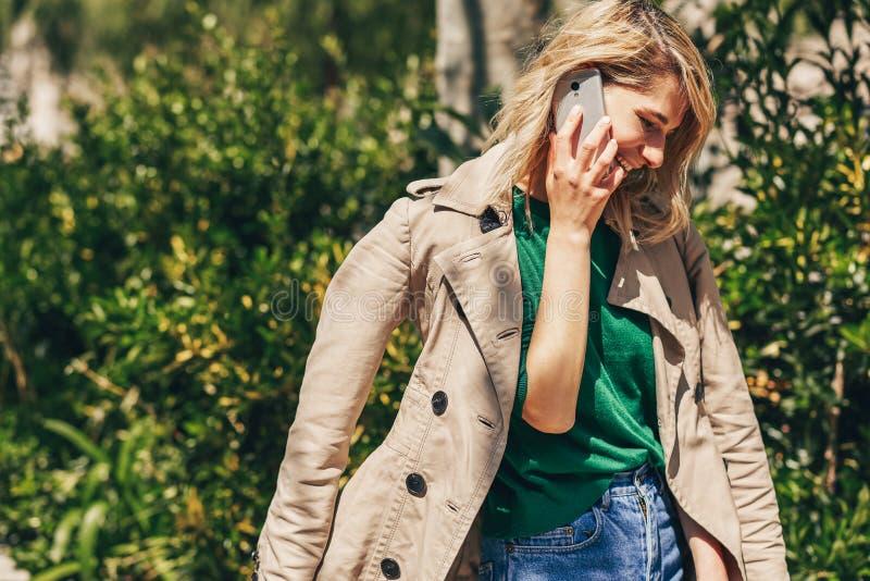 Retrato ascendente cercano del aire libre de la mujer europea joven que sonríe ampliamente mientras que habla en el smartphone, e imagen de archivo