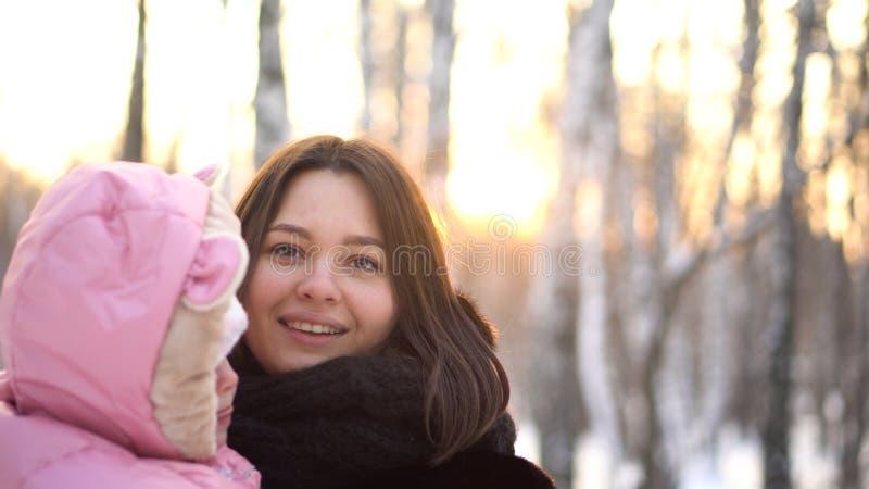 Retrato ascendente cercano del bebé y de su madre joven, hermosa afuera en los árboles nevosos en fondo del parque del invierno M fotos de archivo libres de regalías