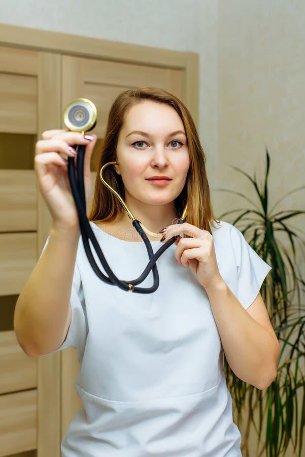 Retrato ascendente cercano del doctor con el estetoscopio en oído Un doctor de sexo femenino With A Stethoscope Listening Médico  imagenes de archivo