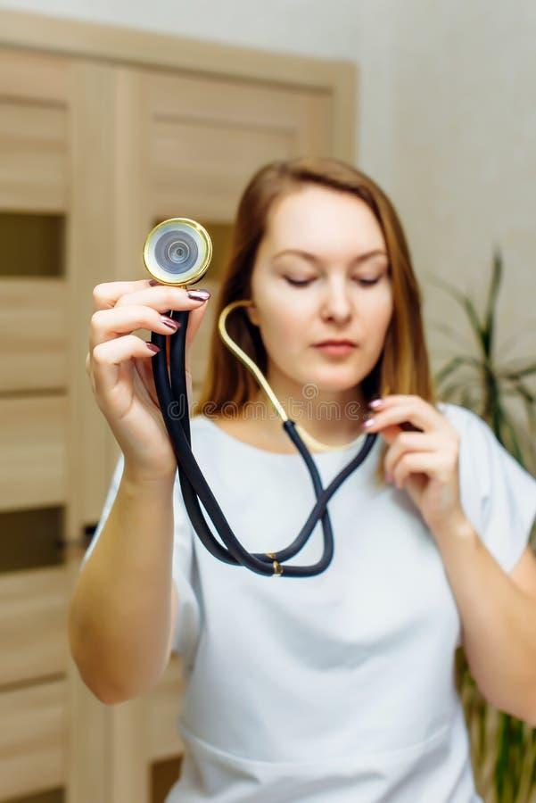 Retrato ascendente cercano del doctor con el estetoscopio en oído Un doctor de sexo femenino With A Stethoscope Listening Médico  imagen de archivo