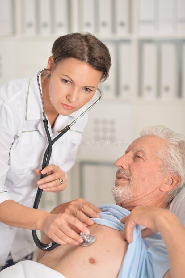 Retrato ascendente cercano del doctor de sexo femenino que examina al paciente mayor imagen de archivo