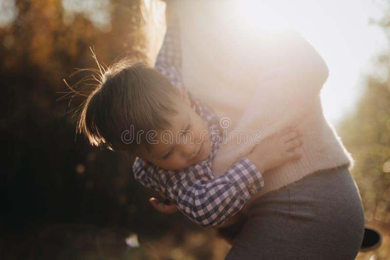 Retrato ascendente cercano del hijo Madre alegre que celebra las manos y que hace girar a su hijo en el muchacho feliz del bosque imagen de archivo