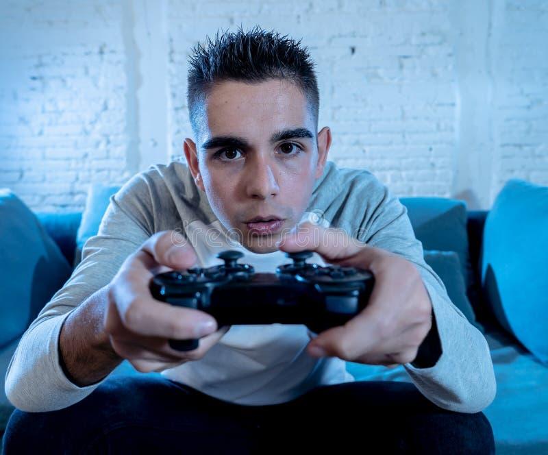 Retrato ascendente cercano del hombre adicto joven que juega al videojuego en la noche en concepto del juego y del apego imagenes de archivo
