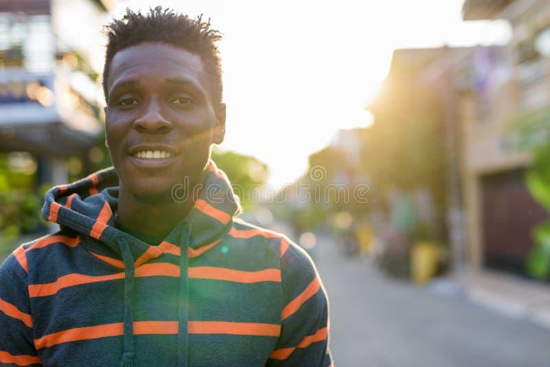 Retrato ascendente cercano del hombre africano negro delgado feliz joven que sonríe al aire libre imágenes de archivo libres de regalías