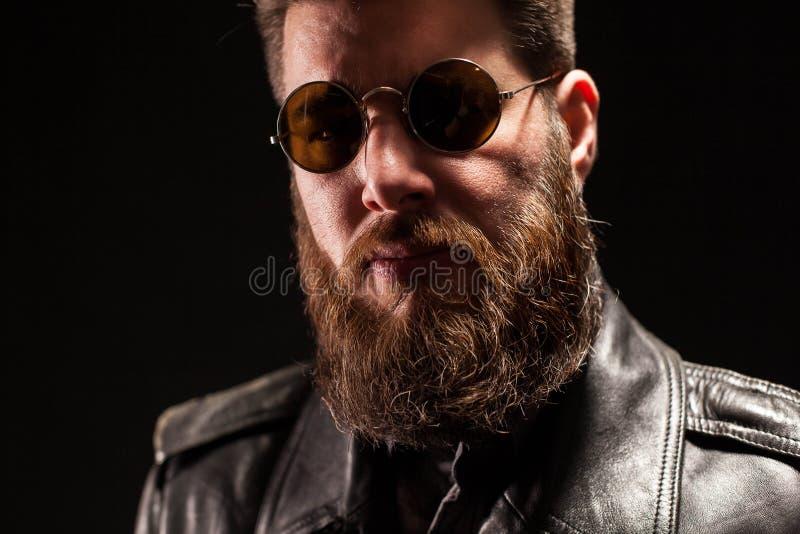 Retrato ascendente cercano del hombre barbudo hermoso serio sobre fondo negro fotos de archivo