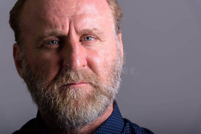 Retrato ascendente cercano del hombre barbudo maduro que mira la cámara fotos de archivo